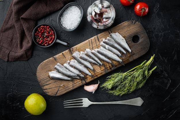 Ingemaakte gezouten ansjovisfilet set, op houten snijplank, op zwarte tafel met kruiden en ingrediënten, bovenaanzicht plat leggen