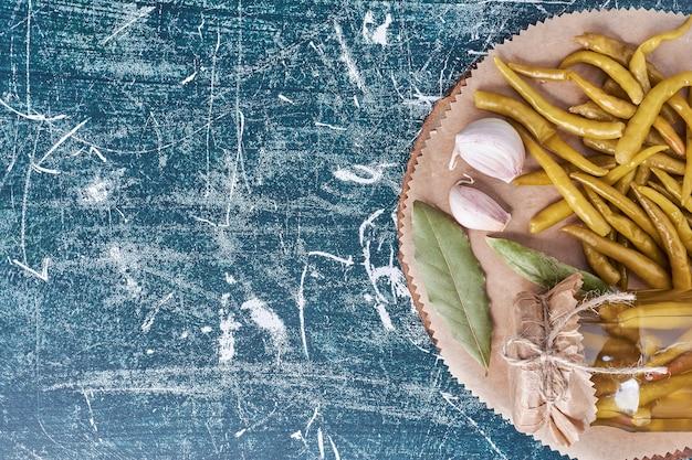 Ingemaakte hete pepers in glazen pot en op plaat met blad en knoflook.