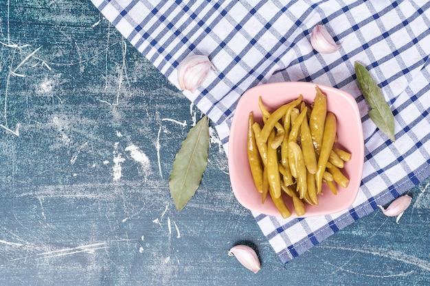 Ingemaakte hete pepers op plaat met blad, knoflook en tafelkleed.