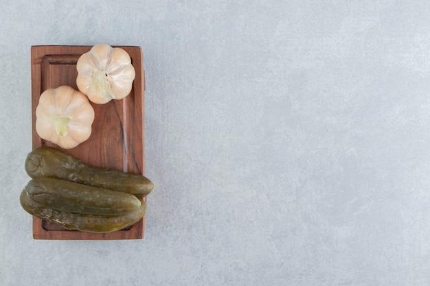 Ingemaakte komkommers en knoflook op een houten bord.