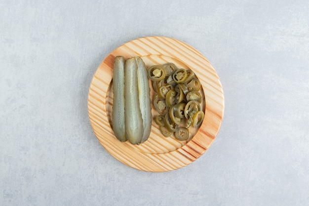 Ingemaakte komkommers en paprika's op houten plaat.