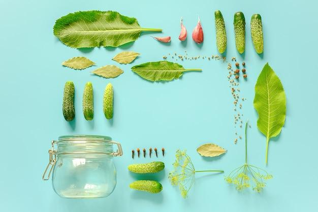 Ingemaakte komkommers. ingrediënten voor gemarineerde augurken en glazen pot frame op blauwe achtergrond. concept culinair recept