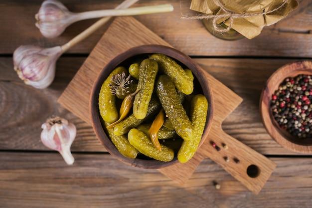 Ingemaakte komkommers, kruiden en knoflook bewaren op een houten tafel. gezond gefermenteerd voedsel. home ingeblikte groenten.