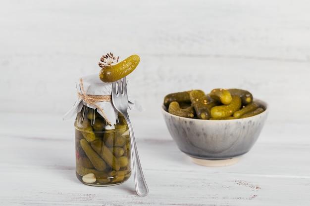 Ingemaakte komkommers, kruiden en knoflook bewaren op een witte houten tafel. gezond gefermenteerd voedsel. home ingeblikte groenten.