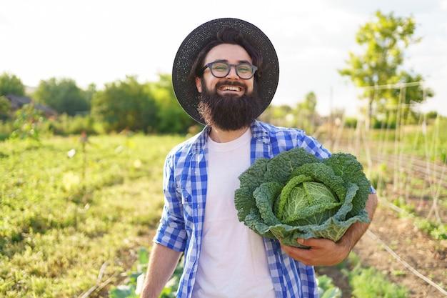 Ingemaakte kool in de handen van een lachende mannelijke boer. man boer met kool op groen gebladerte. oogstconcept