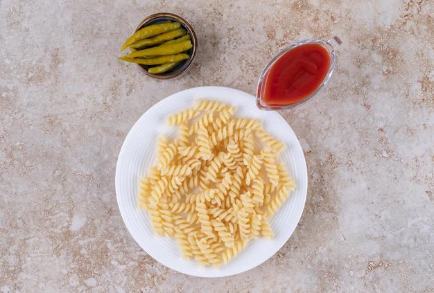 Ingemaakte paprika's, ketchup en macaroni weergegeven op marmeren oppervlak.