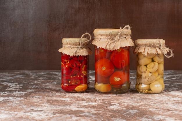 Ingemaakte rode paprika en champignons in een glazen pot op marmeren tafel met kom gepekelde tomaten.