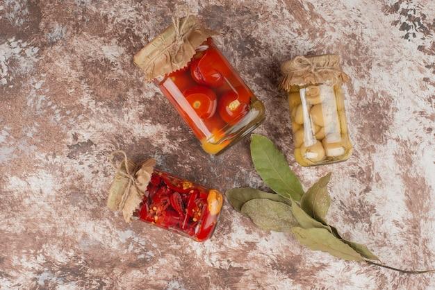 Ingemaakte rode paprika, tomaten en champignons in een glazen pot op marmeren tafel.