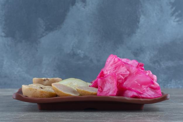 Ingemaakte roze kool met appelschijfjes op bruine plaat.