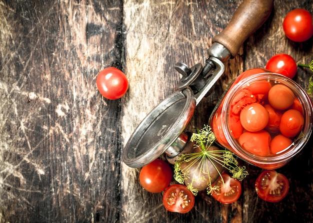 Ingemaakte tomaten met kruiden, specerijen en seamer op een houten tafel.
