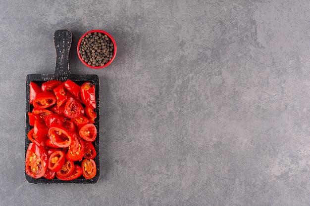 Ingemaakte tomaten met peperkorrels die op een steenlijst worden geplaatst.