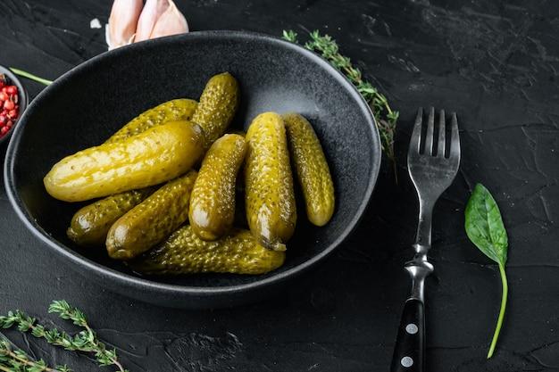 Ingemaakte zelfgemaakte komkommers, augurken set, op zwart