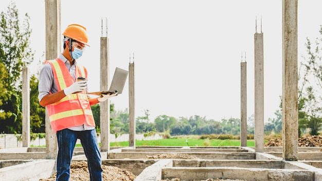 Ingenieur aannemer gebruik laptop werk industrie project controleer huisplan ontwerp op bouwplaats