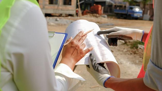 Ingenieur aannemer team vergadering werk industrie project en controleer ontwerp op bouwplaats