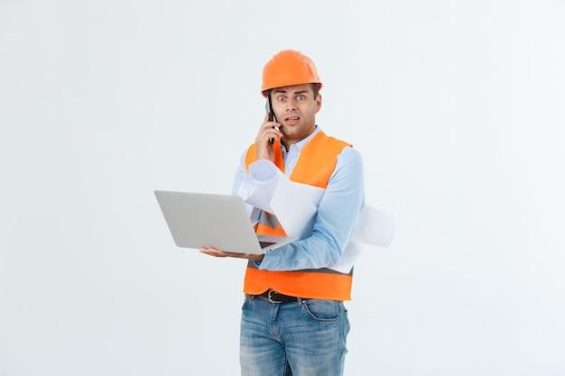 Ingenieur, architect, op druk gezicht spreekt op smartphone terwijl hij blauwdrukken vasthoudt. man, voorman in helm spreken op telefoon, rode achtergrond. architect belt ingenieur om plan te repareren. communicatieconcept.