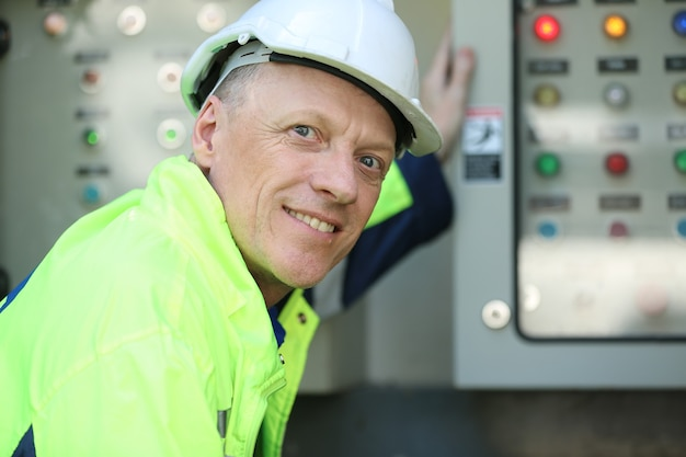 Ingenieur bezig met het controleren en onderhouden van apparatuur op de energieboerderij van zonnepanelen, fotovoltaïsche celpark, groene energieconcept.