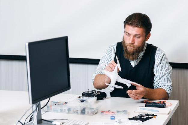 Ingenieur bouwen drone in kantoor, vooraanzicht. manager test nieuw afspeelapparaat tijdens pauze. hobby, technologie, entertainmentconcept
