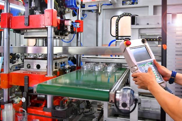 Ingenieur controle en controle automatisering plastic beker op transportband in distributie magazijn.