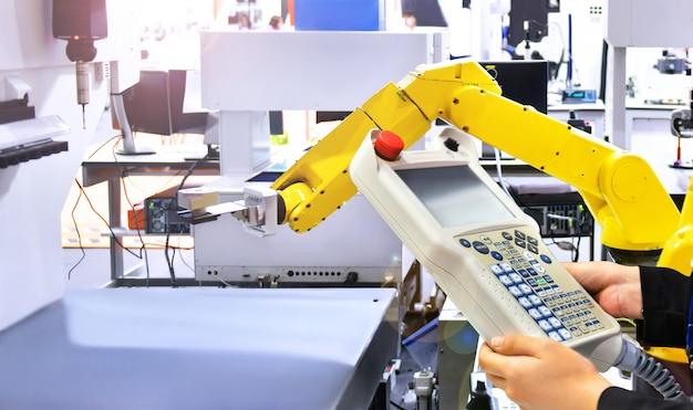 Ingenieur controleert en controleert automatisering geel modern robotsysteem in fabriek, het concept van de industrierobot