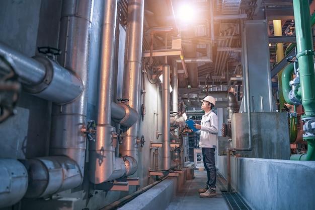 Ingenieur controleert statuswerk in fabriek, stalen pijpleidingen en kleppen in industriële zone, onderhoudsapparatuur voor ingenieurs in energiecentrale.