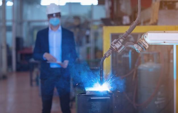 Ingenieur controleren en controleren automatisering robotarmen machine in intelligente fabrieksindustrie op real-time monitoring systeemsoftware.