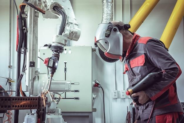 Ingenieur controleren en regelen lasrobotica automatische wapenmachine in intelligente industriële fabrieks automotive