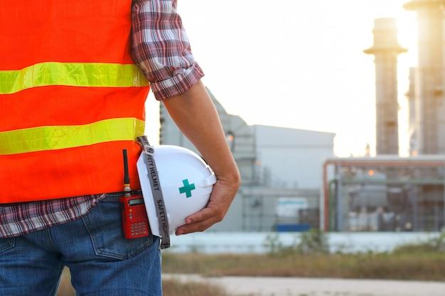 Ingenieur die aan elektrische centrale met veiligheidshelm werkt