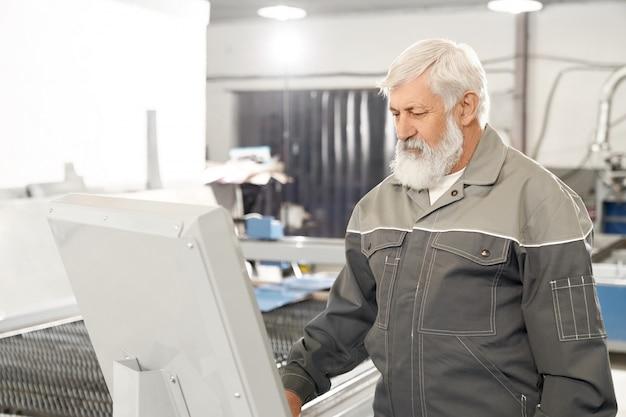 Ingenieur die aan fabriek met geautomatiseerde machine werkt.