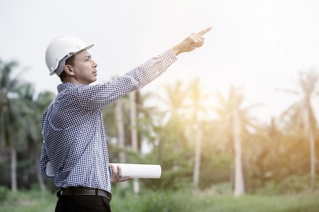Ingenieur die bij bouwwerf werkt om een nieuw projectconcept in het bos te plannen
