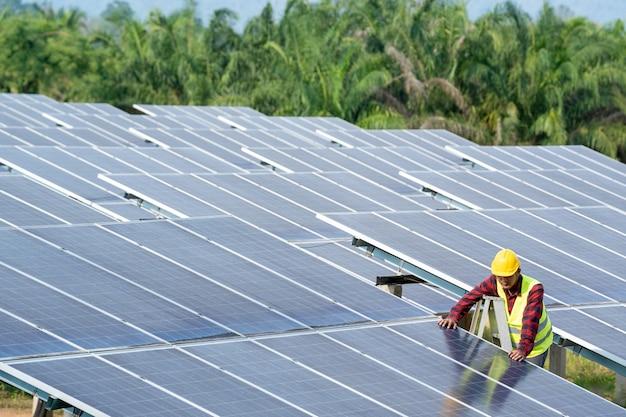 Ingenieur die bij het controleren van en onderhoudsmateriaal bij de industrie zonnemacht werkt, concept groene nieuwe energie.