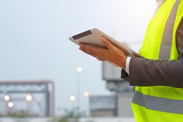 Ingenieur die bij openlucht het controleren van tablet aan bouwterrein werken