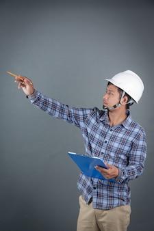 Ingenieur die blauwdrukken houden en nota's over klembord lezen terwijl status op grijze achtergrond.