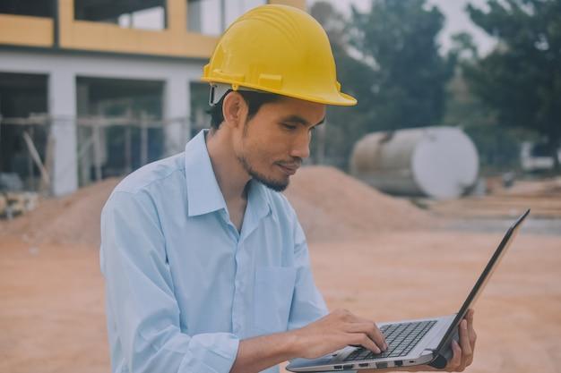 Ingenieur die computer op bouwwerf met behulp van