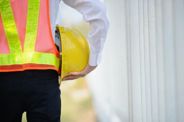 Ingenieur die de gele achtergrond van de de bouwvakkerbouw van de helmveiligheid houden