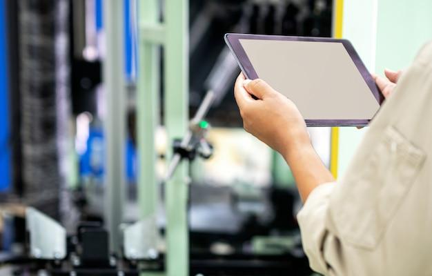 Ingenieur die digitale tablet gebruiken voor het testen van de werking van de machine in de fabrieksfabriek