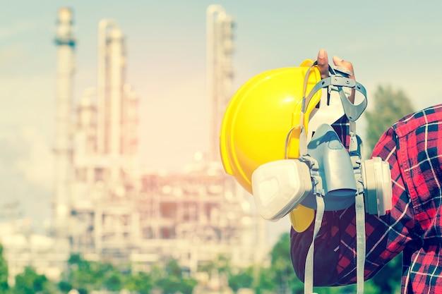 Ingenieur die een gele helm voor de veiligheid houdt