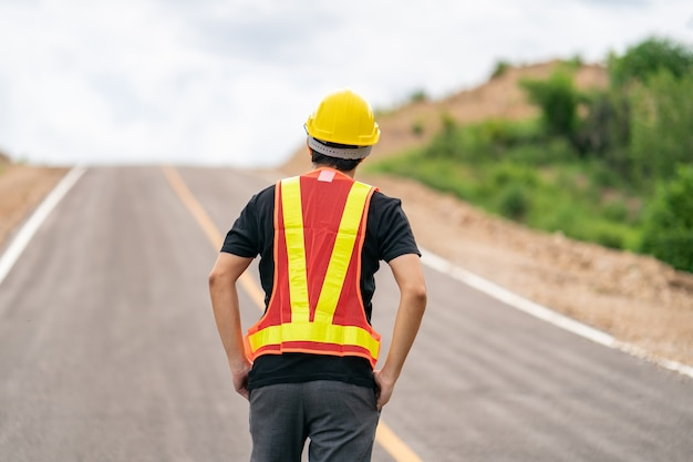 Ingenieur die gele helm draagt voor veiligheid met de weg