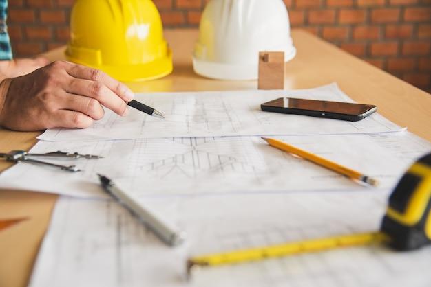 Ingenieur die in bureau met blauwdrukken werkt, inspectie op werkplaats voor architecturaal plan, bouwproject, bedrijfsbouw.