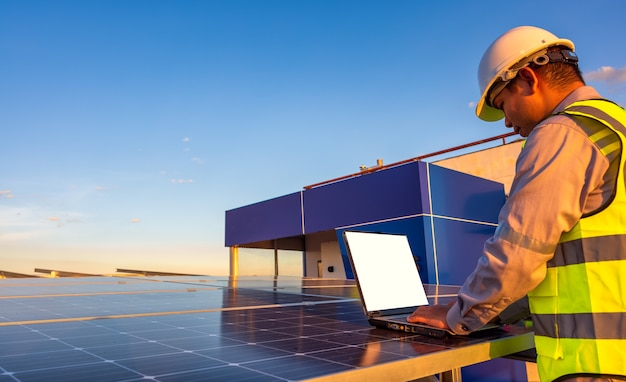 Ingenieur die laptop gebruikt bij zonnepanelen op het dak bij zonsonderganghemel ingenieur die bij een fotovoltaïsche installatie werkt