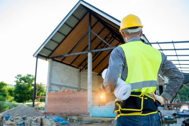 Ingenieur die met blauwdruk op bouwterrein werkt.