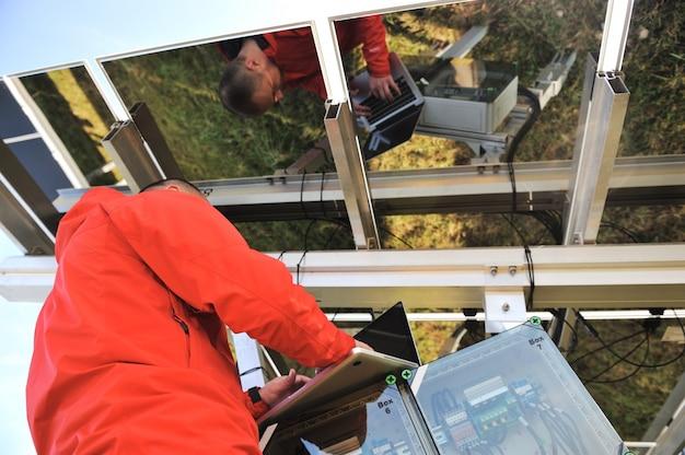 Ingenieur die met laptop het bevestigen zonnepanelen werken