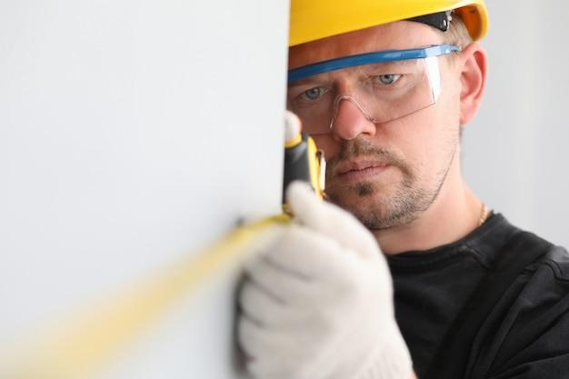 Ingenieur die muurgrootte meet