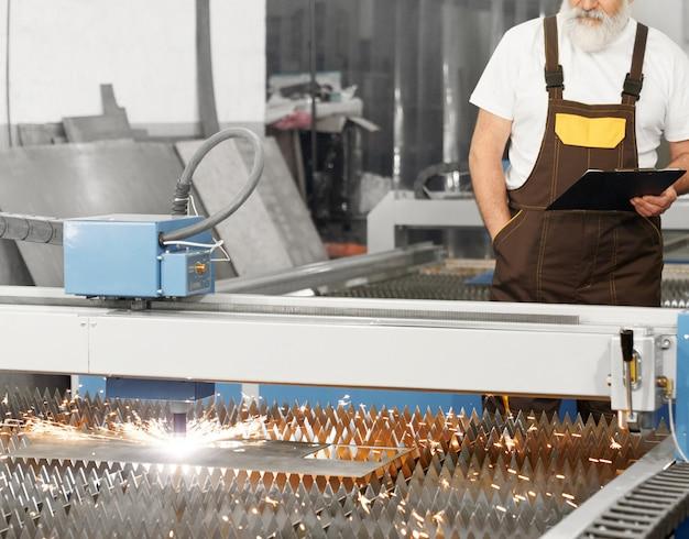Ingenieur die plasma lasersnijdende metaalplaat waarneemt.