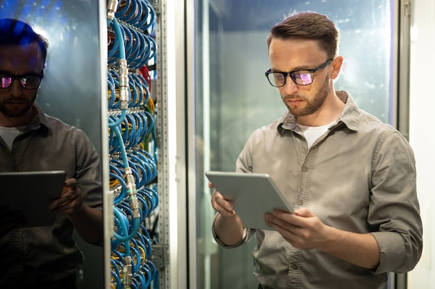 Ingenieur die tablet in serverruimte gebruiken