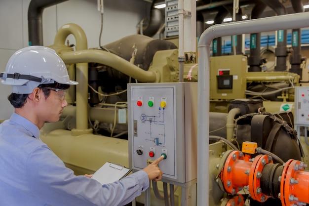 Ingenieur die werkende industriële koelmachines, warm waterpomp en pijplijn controleert voor maakt op hoge temperatuurstoestand in hvac-systemen.
