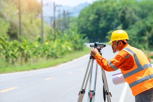 Ingenieur die werkt met theodoliet doorvoerapparatuur op de weg.