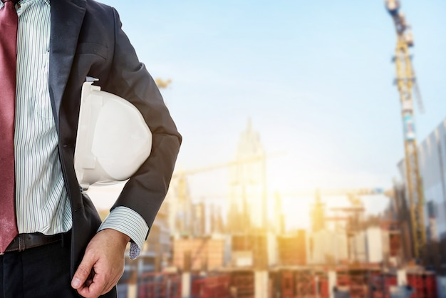 Ingenieur die witte helm voor arbeidersveiligheid houdt op muur van nieuwe highrise flatgebouwen