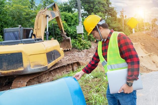 Ingenieur draagt veiligheidsuniform, houdt een laptop vast en onderzoekt de opgraving van de grote pijppleister