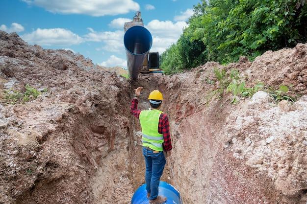 Ingenieur draagt veiligheidsuniform, houdt een laptop vast en onderzoekt de uitgraving van de afvoerpijp
