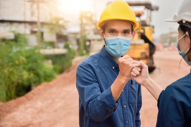 Ingenieur dragen gezichtsmasker hand schudden geen aanraking op de bouwplaats